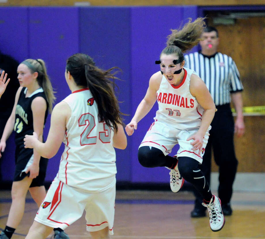 At right, Alexa Moses (#11) of Greenwich  jumps in the air and shouts after Greenwich defeated Trumbull 51-41 in the FCIAC girls high school basketball quarterfinal playoff gamel at Westhill High School in Stamford, Conn., Saturday, Feb. 21, 2015. At left walking off the court is Trumbull's Danielle McGillicuddy (#14) and at center is Jamie Kockenmeister (#23) of Greenwich. Photo: Bob Luckey / Greenwich Time