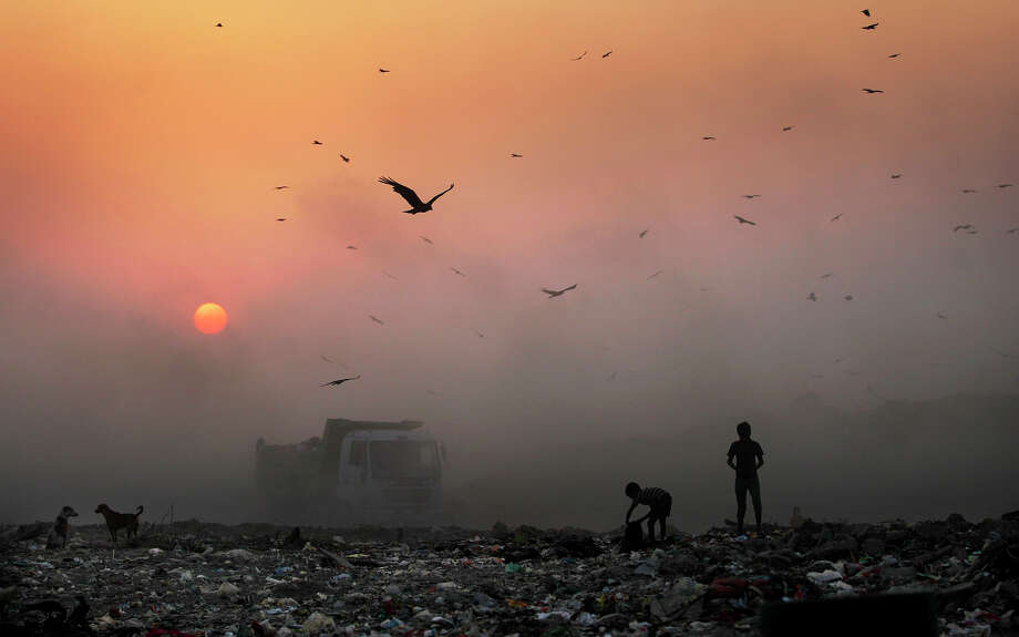 The sun sets behind a thick blanket of smog as young ragpickers search a dump in New Delhi. Photo: Altaf Qadri / Associated Press / AP