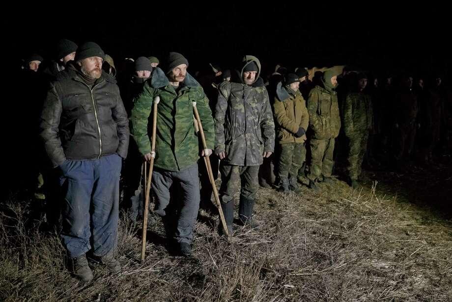 Ukrainian prisoners of war wait in formation before a prisoner exchange in separatist-controlled territory near Zholobok, Ukraine. Photo: Vadim Ghirda / Associated Press / AP