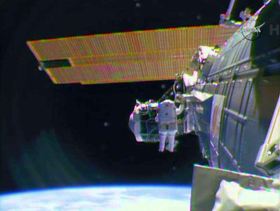 """In this image from television astronaut Barry """"Butch"""" Wilmore begins the spacewalk Saturday morning Feb. 21, 2015 to wire the International Space Station in preparation for the arrival in July of the international docking port for the Boeing and Space-X commercial crew vehicles. (AP Photo/NASA-TV) Photo: Associated Press"""