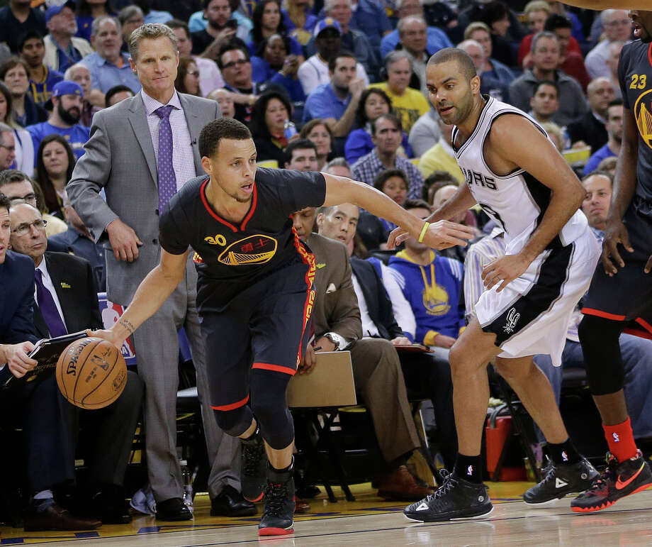 Golden State Warriors' Stephen Curry dribbles next to San Antonio Spurs' Tony Parker during the second half of an NBA basketball game Friday, Feb. 20, 2015, in Oakland, Calif. Standing at left rear is Warriors coach Steve Kerr.  Golden State won 110-99. (AP Photo/Marcio Jose Sanchez) Photo: Marcio Jose Sanchez, STF / Associated Press / AP