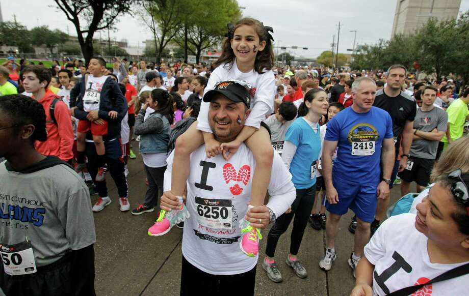 Sean Seger holds his daughter, Alexis Seger, 7, on his shoulders as they wait for the start of the 10th Annual Steps-for-Students 5K Run/Walk, held at the Co-Cathedral of the Sacred Heart, 1111 St. Joseph Parkway, Saturday, Feb. 21, 2015, in Houston. Photo: Melissa Phillip, Houston Chronicle / © 2014  Houston Chronicle