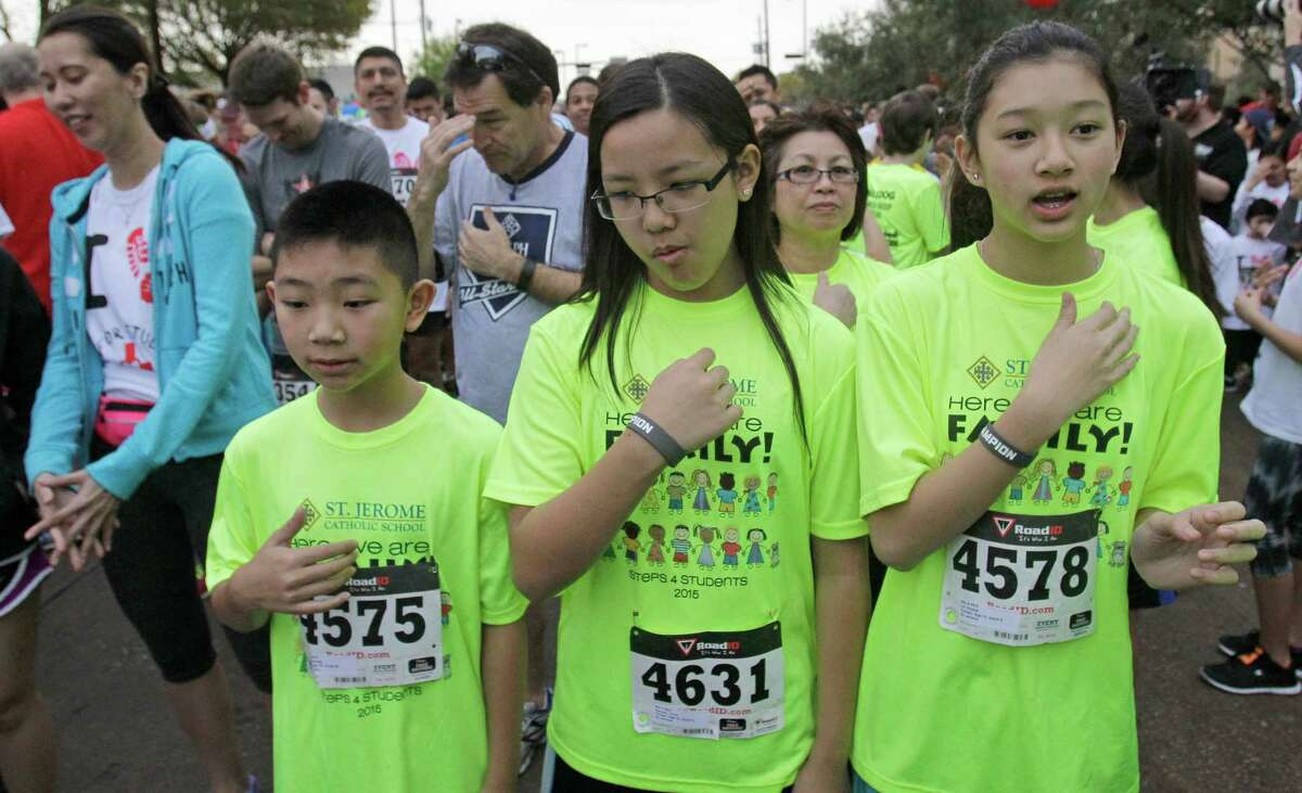 St. Jerome Catholic School students Kennedy Le, 12, left, Trinh Nguyen, 13, center, and Krystal Le, 13, right, make the sign of the cross after a prayer before the start of the 10th Annual Steps-for-Students 5K Run/Walk, held at the Co-Cathedral of the Sacred Heart, 1111 St. Joseph Parkway, Saturday, Feb. 21, 2015, in Houston.