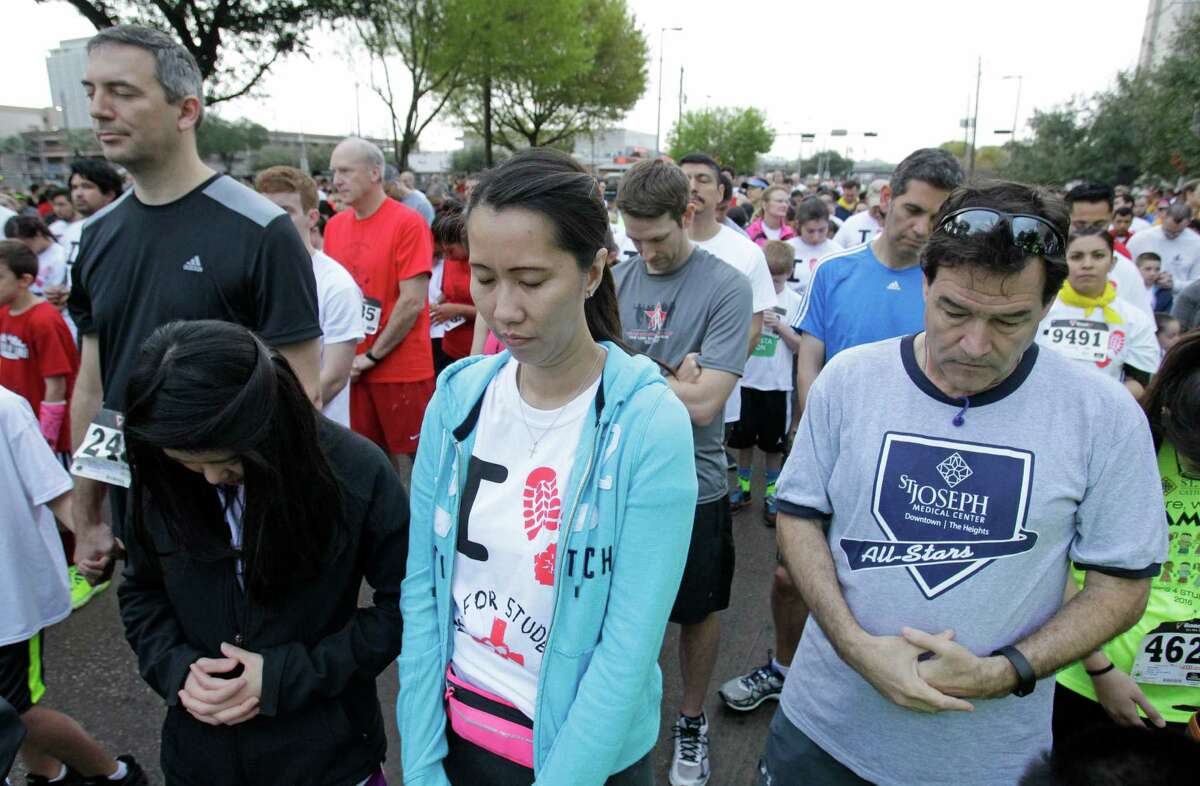 People pray before the start of the 10th Annual Steps-for-Students 5K Run/Walk, held at the Co-Cathedral of the Sacred Heart, 1111 St. Joseph Parkway, Saturday, Feb. 21, 2015, in Houston.