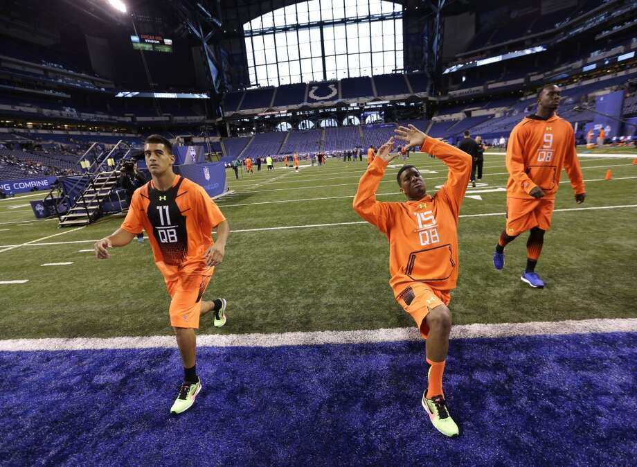 Florida State quarterback Jameis Winston (15) and Oregon quarterback Marcus Mariota (11)  stretch at the NFL football scouting combine in Indianapolis, Saturday, Feb. 21, 2015. (AP Photo/David J. Phillip) Photo: Associated Press