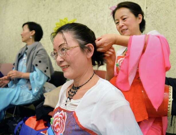 Chinese Cultural Dance Troupe's Lisa Jiang, center, of Niskayuna has her hair tied back by fellow dancer Aiping Gu of Latham, right, before their performance in NYS Capital Region 2015 Chinese New Year Celebration at the Performing Arts Center at SUNY Albany Campus Saturday Feb. 21, 2015, in Albany, NY.  (John Carl D'Annibale / Times Union) Photo: John Carl D'Annibale / 00030681A