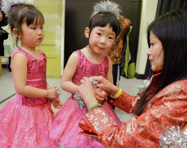 The Chinese Cultural School dancers Aimee Cao, 4, left, of Latham and Emma Tian, 4, of Niskayuna with instructor Baozhen Huang before their performance in the NYS Capital Region 2015 Chinese New Year Celebration in the  Performing Arts Center at SUNY Albany Campus Saturday Feb. 21, 2015, in Albany, NY.  (John Carl D'Annibale / Times Union) Photo: John Carl D'Annibale / 00030681A