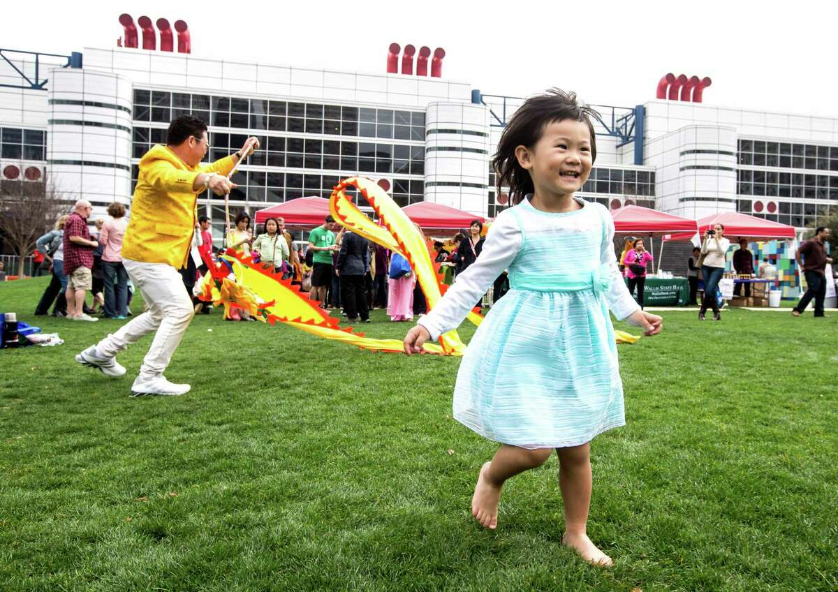Cindy Lee runs in the grass during the 19th Annual Texas Lunar New Year Celebration at Discovery Green on Saturday, Feb. 21, 2015, in Houston.