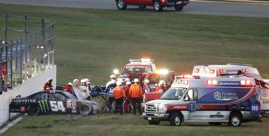 Kyle Busch (center) is taken to an ambulance on a stretcher after his wreck. Photo: John Raoux / Associated Press / AP