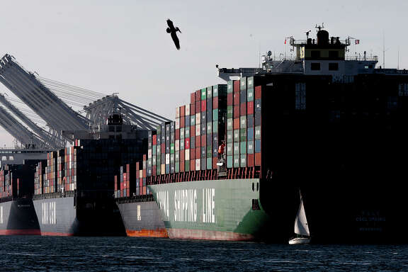 Cargo ships filled with containers are lined up along the docks at the Port of Oakland in February, after the International Longshore and Warehouse Union reached a tentative agreement on a new five-year contract.
