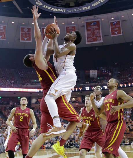 Texas' Isaiah Taylor, right, goes through Iowa State's Georges Niang on his way to a basket in the second half Saturday in Austin. Taylor scored 23 points in the Longhorns' loss, their sixth in the last nine games. Photo: Eric Gay, STF / AP