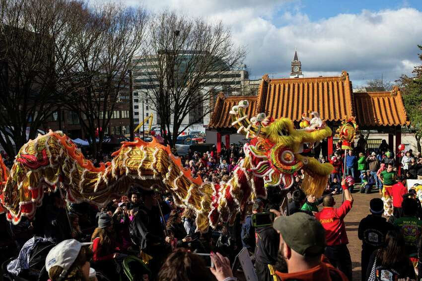Hoisting ornate lion figurines, Mak Fai Kung Fu Club members approach Hing Hay Park to ring in the Year of the Sheep during the annual Lunar New Year Celebration Saturday, February 21, 2015, within Chinatown in Seattle, Washington. The day-long celebration includes traditional dragon and lion dances, Japanese Taiko Drumming, martial arts, delicious foods and crafting.