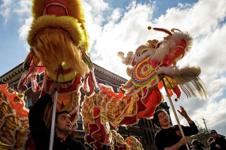 Hoisting ornate lion figurines, Mak Fai Kung Fu Club members approach Hing Hay Park to ring in the Year of the Sheep during the annual Lunar New Year Celebration Saturday, February 21, 2015, within Chinatown in Seattle, Washington. The day-long celebration includes traditional dragon and lion dances, Japanese Taiko Drumming, martial arts, delicious foods and crafting. Photo: JORDAN STEAD, SEATTLEPI.COM / SEATTLEPI.COM
