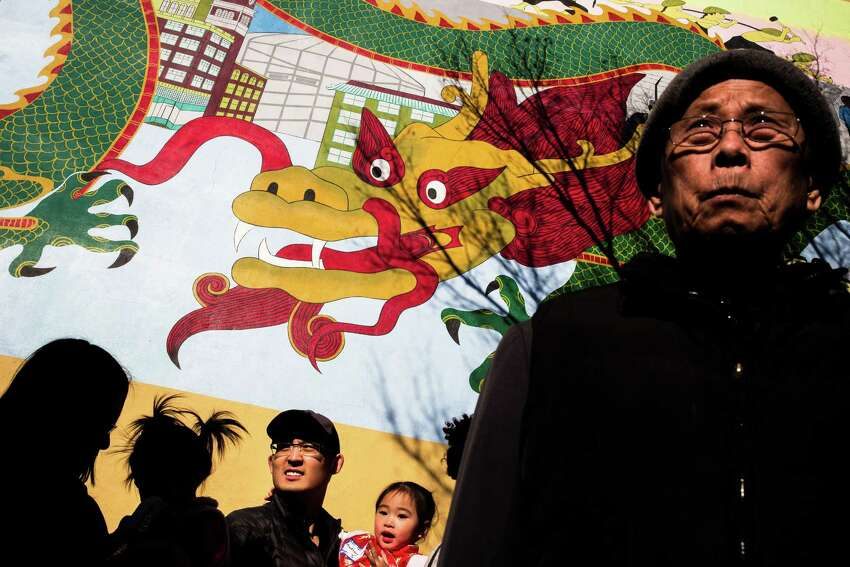 Families and dressed up children await a costume contest under a large dragon mural during the annual Lunar New Year Celebration Saturday, February 21, 2015, within Chinatown in Seattle, Washington. The day-long celebration includes traditional dragon and lion dances, Japanese Taiko Drumming, martial arts, delicious foods and crafting.