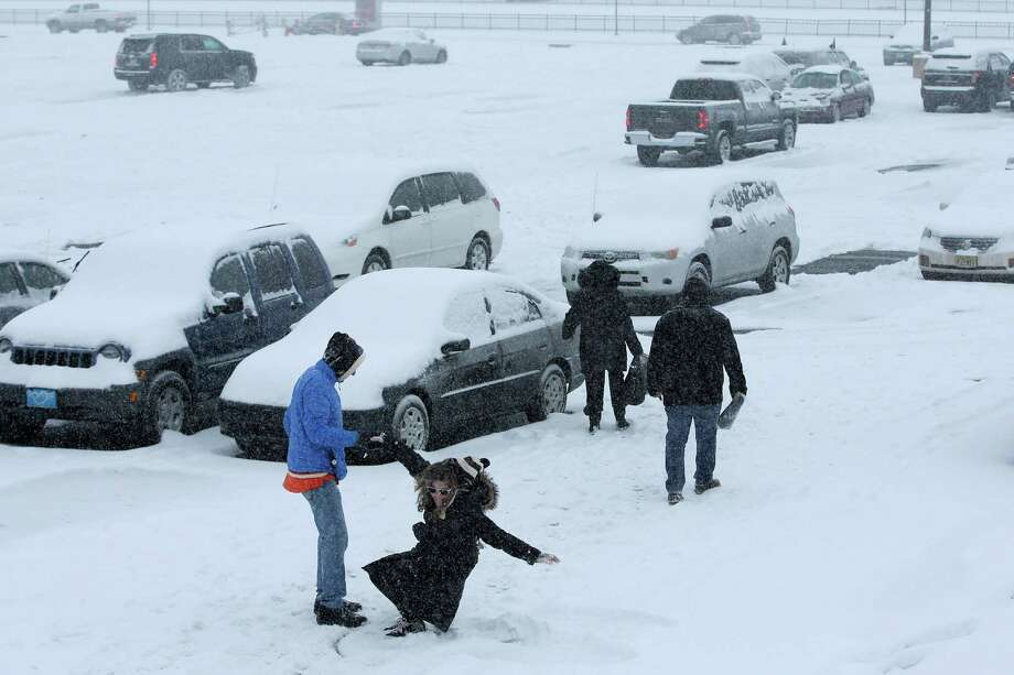 A woman is helped up after making a snow angel in a parking lot outside the Wells Fargo Center during a winter storm after an NHL hockey game between the Philadelphia Flyers and the Nashville Predators, Saturday, Feb. 21, 2015, in Philadelphia. (AP Photo/Matt Slocum) Photo: Matt Slocum, STF / AP