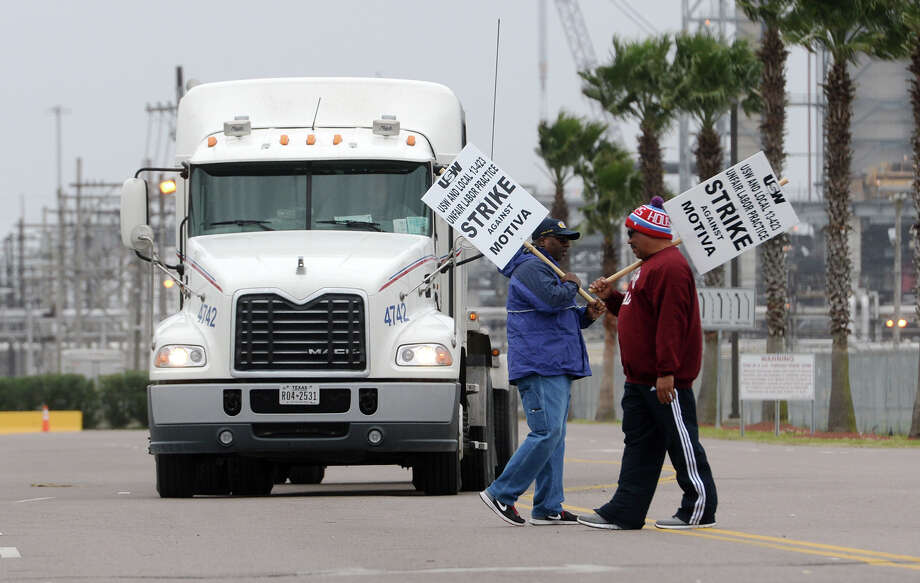 A pair of tanker trucks slow down as Darrell Henson, left, and Vincent Hilts picket across the entrance to the Motiva plant in Port Arthur on Saturday.  Photo: Jake Daniels / ©2014 The Beaumont Enterprise/Jake Daniels