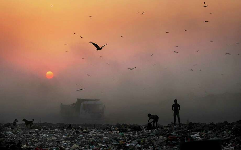 FILE- In this Oct. 17, 2014, file photo, a thick blanket of smoke is seen against the setting sun as young ragpickers search for reusable material at a garbage dump in New Delhi, India. India's filthy air is cutting 660 million lives short by about three years, while nearly all of the country's 1.2 billion citizens are breathing in harmful pollution levels, according to research published Saturday, Feb. 21. While New Delhi last year earned the dubious title of being the world's most polluted city, the problem extends nationwide, with 13 Indian cities now on the World Health Organization's list of the 20 most polluted. (AP Photo/Altaf Qadri, File) Photo: Altaf Qadri, STR / AP