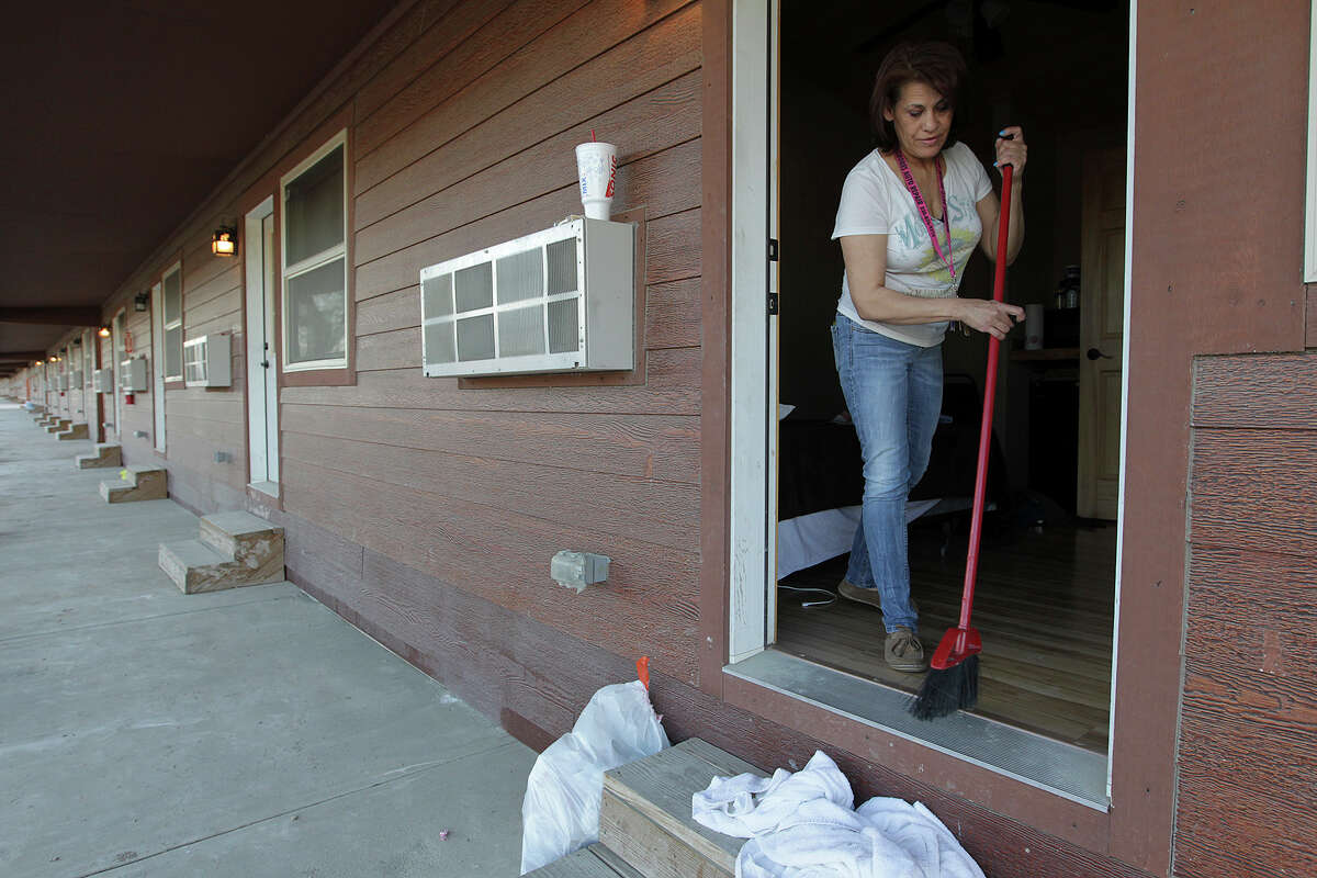 After the second shift leaves in the late afternoon Wednesday, Sandy Jaime, 53, cleans up a unit at the Double C Resort near Carrizo Springs. The resort's clients are mostly large oil-field companies that rent rooms by volume.