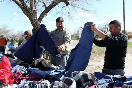 From left, Juan Fuentes, Daniel Sanchez and Abe Jimenez, from Laredo, look over used fire-resistant clothing Thursday at a stall in a parking lot in Tilden. Photo: Jerry Lara /San Antonio Express-News / © 2015 San Antonio Express-News