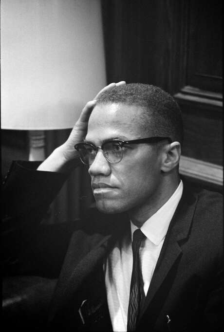 Malcolm X listens as Martin Luther King Jr. talks to reporters on March 26, 1964. They met only once, a grip-and-grin for cameras as they passed in a Capitol Hill hallway after observing a filibuster over the proposed Civil Rights Act. Over time, Malcolm's respect for King increased. Illustrates MALCOLMX (category l), by Krissah Thompson  2015, The Washington Post. Moved Friday, Feb. 20, 2015. (MUST CREDIT: By Marion S. Trikosko, U.S. News & World Report Magazine Photograph Collection/ Library of Congress Prints and Photographs Division) Photo: HANDOUT, STR / THE WASHINGTON POST