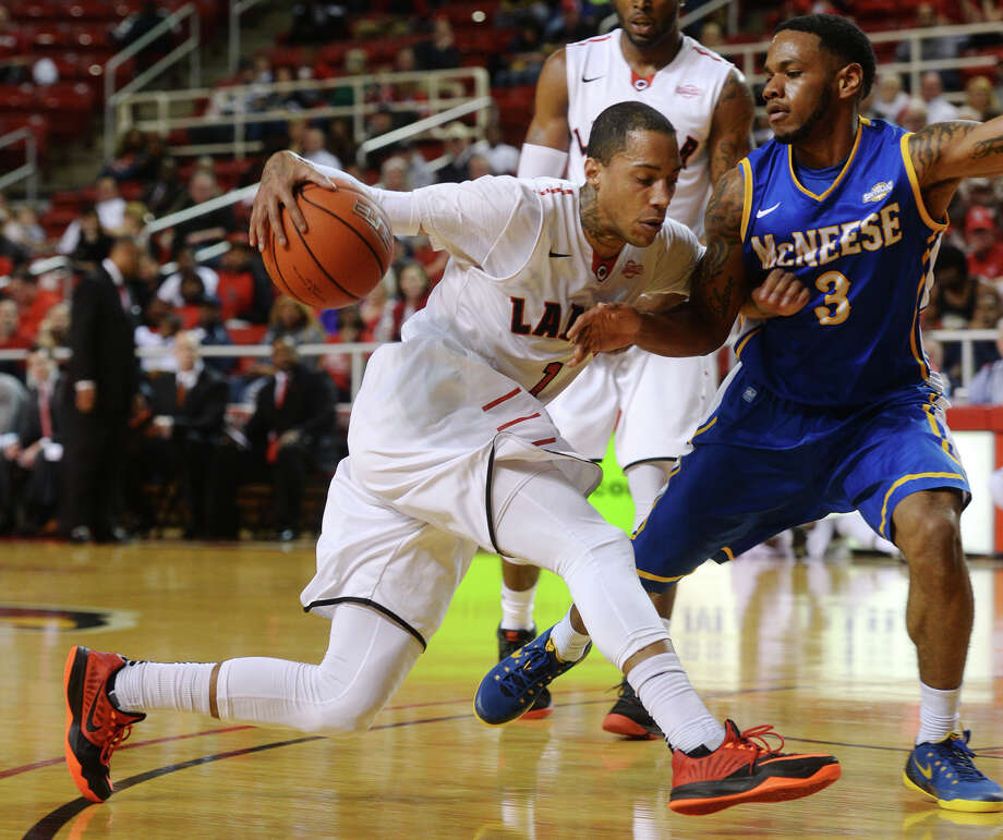 Lamar's Anthony Holliday, No. 1, tries to advance against McNeese's Keelan Garrett, No. 3, on Saturday. The Lamar Cardinals hosted the McNeese State Cowboys at the Montagne Center on Saturday night. Photo taken Saturday 2/21/15 Jake Daniels/The Enterprise Photo: Jake Daniels / ©2014 The Beaumont Enterprise/Jake Daniels