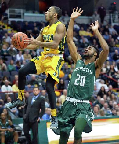 Siena's #5 Evan Hymes, left, gets some altitude on Manhattan's #20 Jermaine Lawrence during a MAAC game at the Times Union Center Saturday Feb. 21, 2015 in Albany, NY.  (John Carl D'Annibale / Times Union) Photo: John Carl D'Annibale / 00030520C