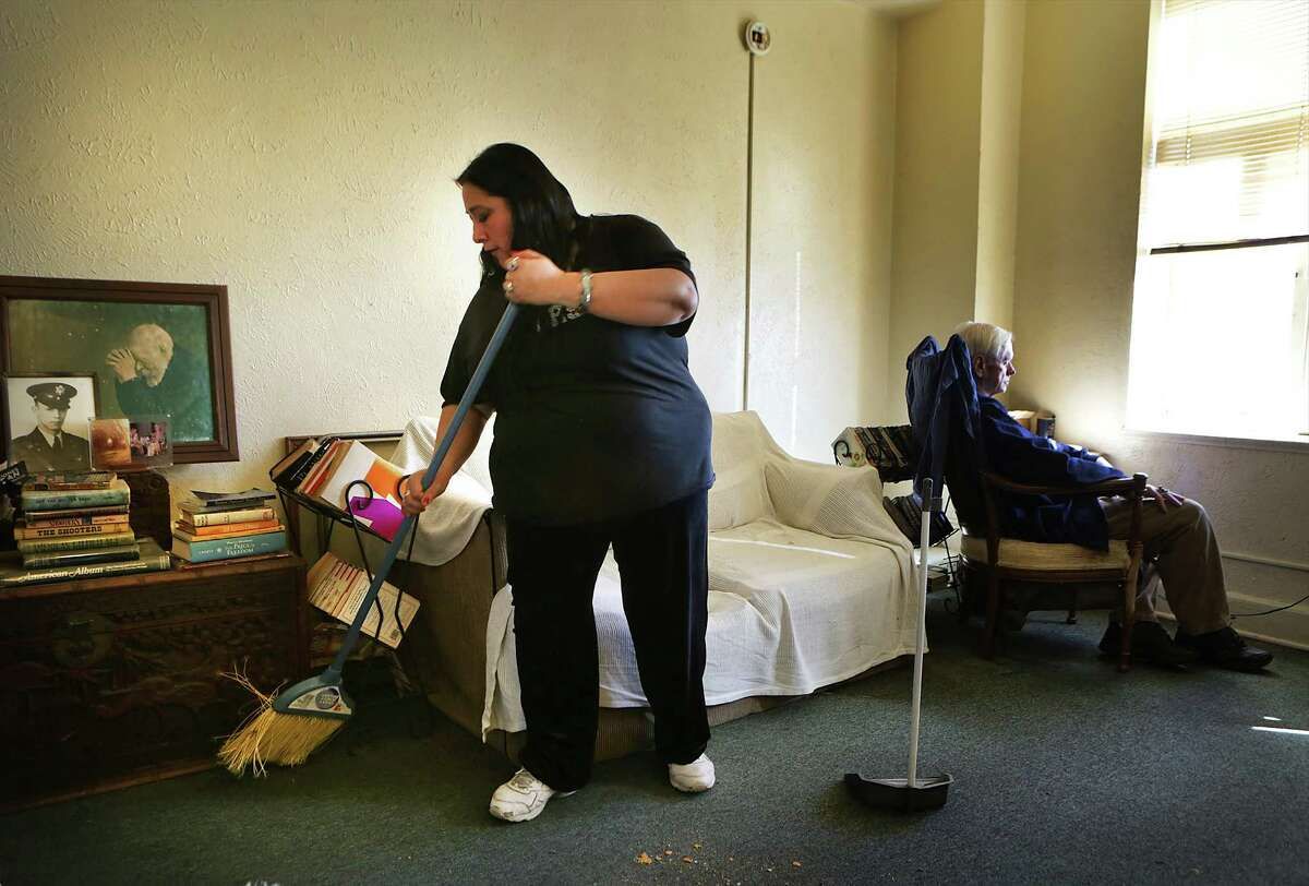 John Reynolds, right, a resident on the 5th floor of the Aurora Apartments, sits in his favorite chair by an open window as his care taker Blanca Olmeda sweeps. The apartment building doesn't have sprinkler systems. Tuesday, Jan. 27, 2015.