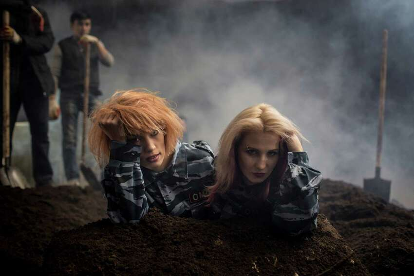 In this photo taken on Monday, Jan. 26, 2015, two members of the punk band Pussy Riot, Maria Alekhina and Nadezhda Tolokonnikova, left, perform during their music video clip in Moscow, Russia. Two members of the punk provocateur band Pussy Riot have released a new music video dedicated to Eric Garner, an unarmed man who was killed when a New York City police officer put him in a fatal chokehold. In their video, Maria Alekhina and Nadezhda Tolokonnikova are dressed in Russian riot police uniforms and shown buried alive. The song is titled