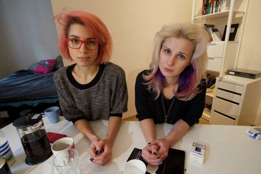 Two members of the punk provocateur band Pussy Riot Maria Alekhina, right, and Nadezhda Tolokonnikova pose for a photo, during an interview with The Associated Press, in Moscow, Russia, Thursday, Feb. 19, 2015. Two members of the punk provocateur band Pussy Riot have released a new music video dedicated to Eric Garner, an unarmed man who was killed when a New York City police officer put him in a fatal chokehold. In the video the are dressed in Russian riot police uniforms and shown buried alive. The song is titled