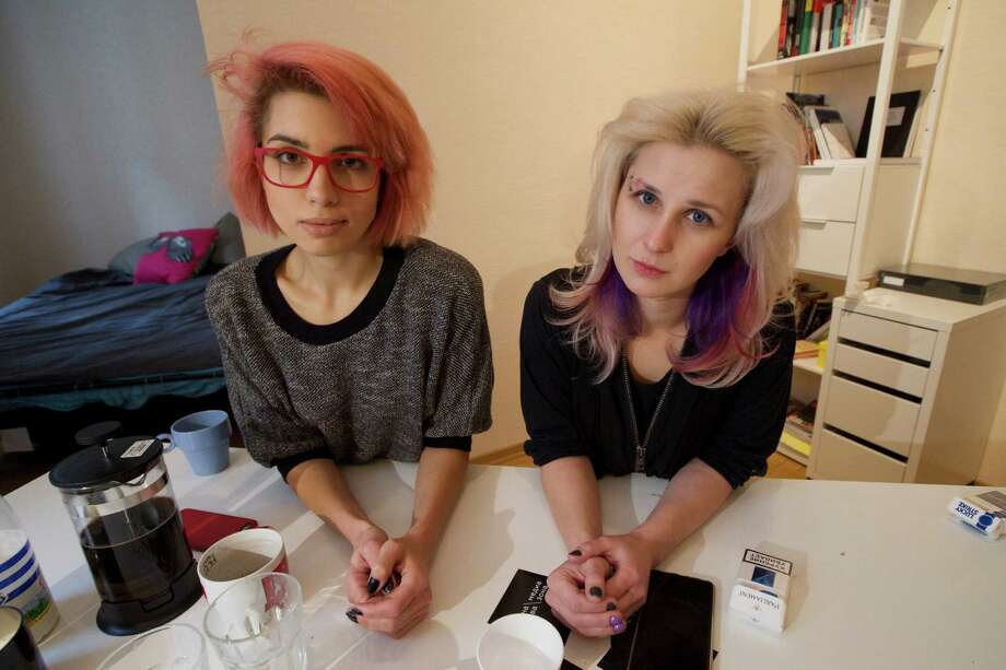 """Two members of the punk provocateur band Pussy Riot Maria Alekhina, right, and Nadezhda Tolokonnikova pose for a photo, during an interview with The Associated Press, in Moscow, Russia, Thursday, Feb. 19, 2015. Two members of the punk provocateur band Pussy Riot have released a new music video dedicated to Eric Garner, an unarmed man who was killed when a New York City police officer put him in a fatal chokehold. In the video the are dressed in Russian riot police uniforms and shown buried alive. The song is titled """"I Can't Breathe,"""" the last words of Eric Garner captured on video by a bystander. Photo: Ivan Sekretarev, AP / AP"""
