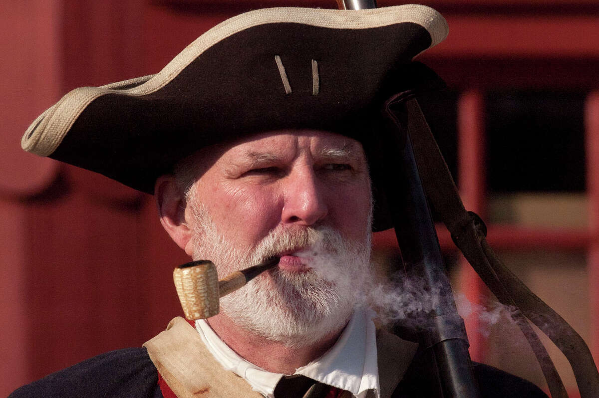 Mike Zap, a reenactor with the 5th Connecticut Regiment, smokes a corn cob pipe while standing at attention during the Putnam Hill Park Rededication and American Revolutionary War Reenactment at Putnam Cottage in Greenwich, Conn., on Sunday, Feb. 22, 2015.