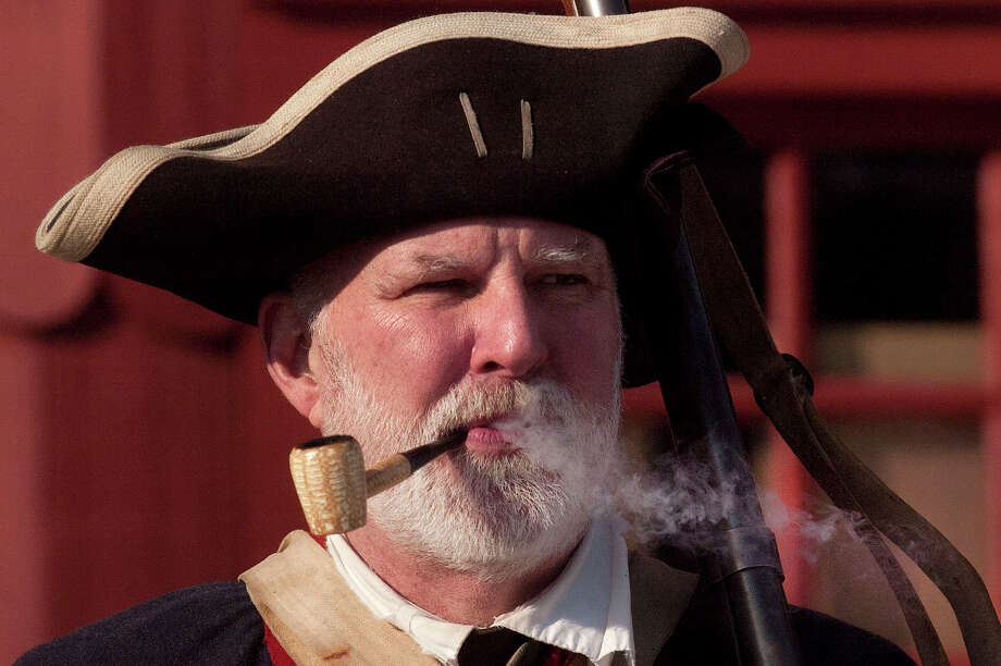 Mike Zap, a reenactor with the 5th Connecticut Regiment, smokes a corn cob pipe while standing at attention during the Putnam Hill Park Rededication and American Revolutionary War Reenactment at Putnam Cottage in Greenwich, Conn., on Sunday, Feb. 22, 2015. Photo: Jason Rearick / Stamford Advocate
