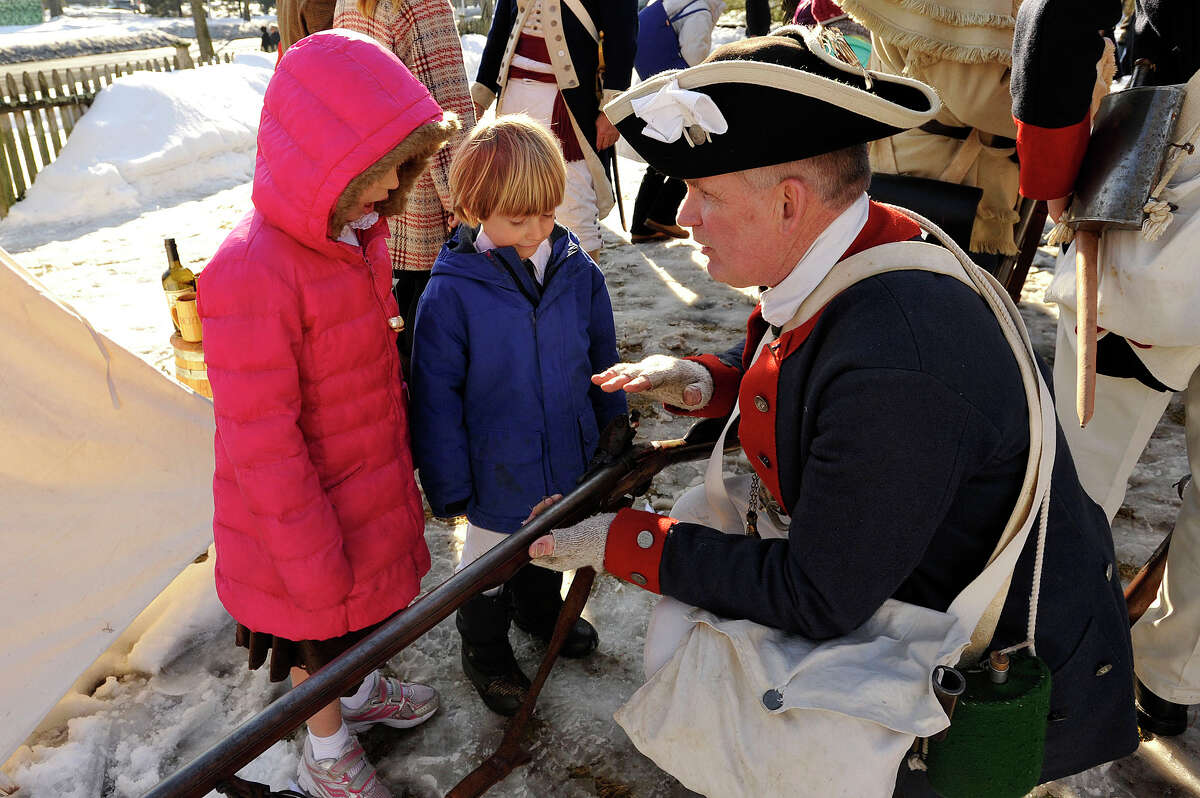 Ray Stuart, a reenactor with the 5th Connecticut Regiment, shows off his Brown Bess musket to Anna and Thomas Oliver during the Putnam Hill Park Rededication and American Revolutionary War Reenactment at Putnam Cottage in Greenwich, Conn., on Sunday, Feb. 22, 2015.