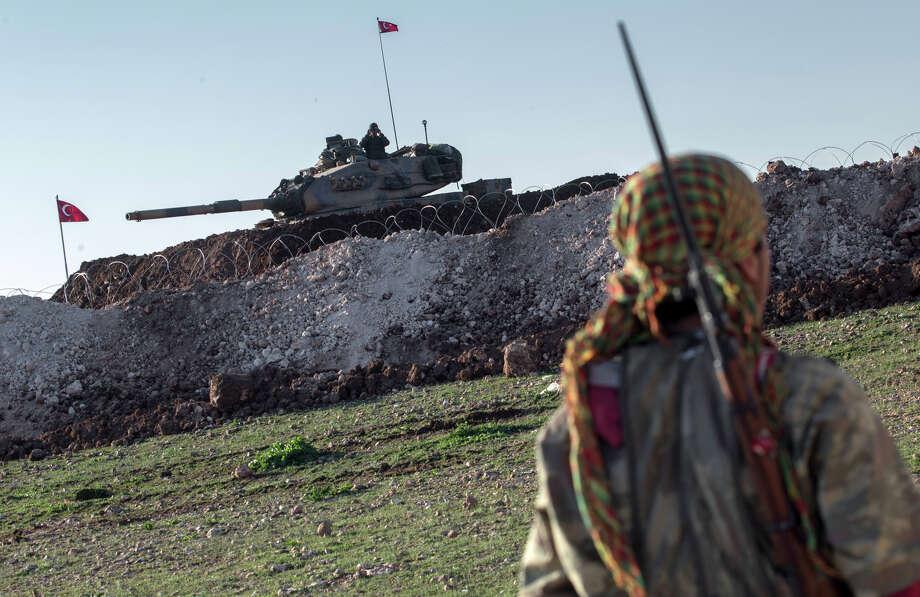 A Syrian Kurdish militia member patrols near a Turkish army tank as troops build a new Ottoman tomb. Photo: Mursel Coban / Associated Press / Depo Photos