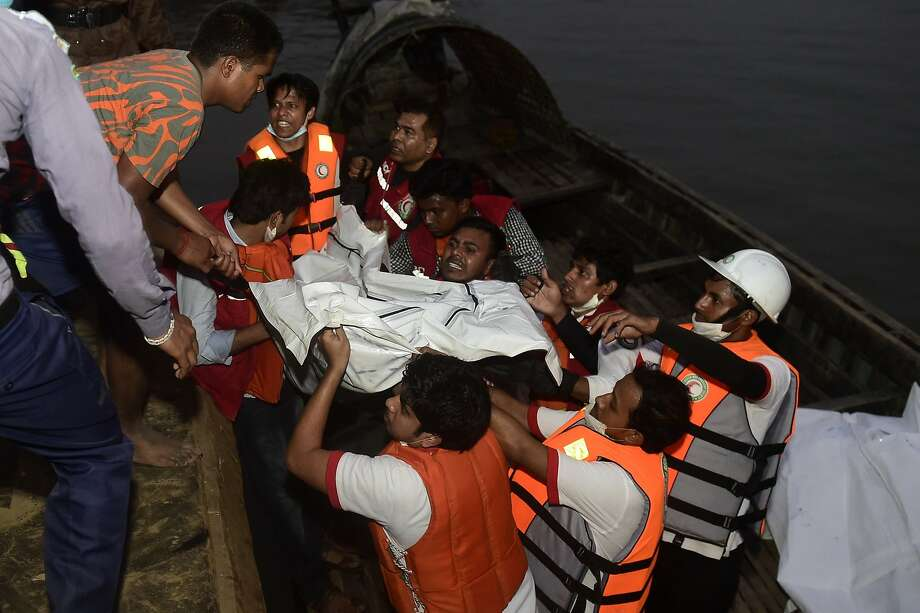 Bangladeshi rescue workers recover the body of a victim after a ferry accident at Paturia some 70kms east of Dhaka on February 22, 2015.   Sixteen people including a baby are confirmed dead and rescuers are still searching for missing passengers after a ferry collided with a cargo ship and sank in a Bangladesh river, officials said. It was the second deadly boat accident in less than a fortnight in the country, which has a history of ferry tragedies.   AFP PHOTO/Munir uz ZAMANMUNIR UZ ZAMAN/AFP/Getty Images Photo: Munir Uz Zaman, AFP / Getty Images