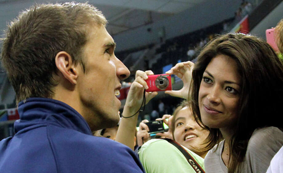 FILE - In this July 29, 2011 file photo, U.S. swimmerMichael Phelps talks to his girlfriend Nicole Johnson, right, after the medal ceremony for the men's 4x200 Freestyle Relay, at the FINA Swimming World Championships in Shanghai, China. The 18-time Olympic gold medalist on Sunday, Feb. 22, 2015 announced on Twitter he's marrying Johnson, who was Miss California in 2010 and has dated Phelps on and off the past few years. (AP Photo/Wong Maye-E, File) Photo: Wong Maye-E / Associated Press / AP