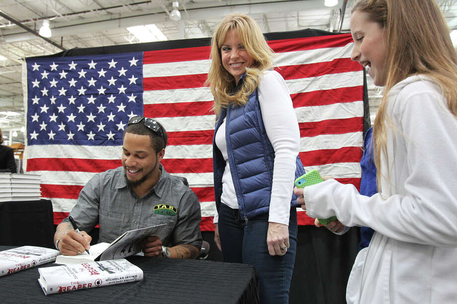 Margie Travis enjoys getting an autograph with her daughter Caroline on hand as Former Army Ranger Nicholas Irving, author of 'The Reaper - Autobiography of one of the Deadliest Special Ops Snipers', signs copies of his book at Costco store 693 in San Antonio on February 7, 2015. Photo: Tom Reel, San Antonio Express-News