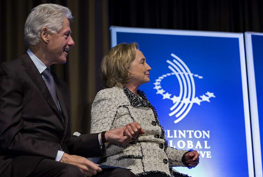 Former President Bill Clinton and former Secretary of State Hillary Clinton holds hands after she introduced Rio de Janiero Mayor Eduardo Paes at the Clinton Global Initiative Mid-Year Meeting in 2013 in New York.  Photo: Craig Ruttle, Associated Press