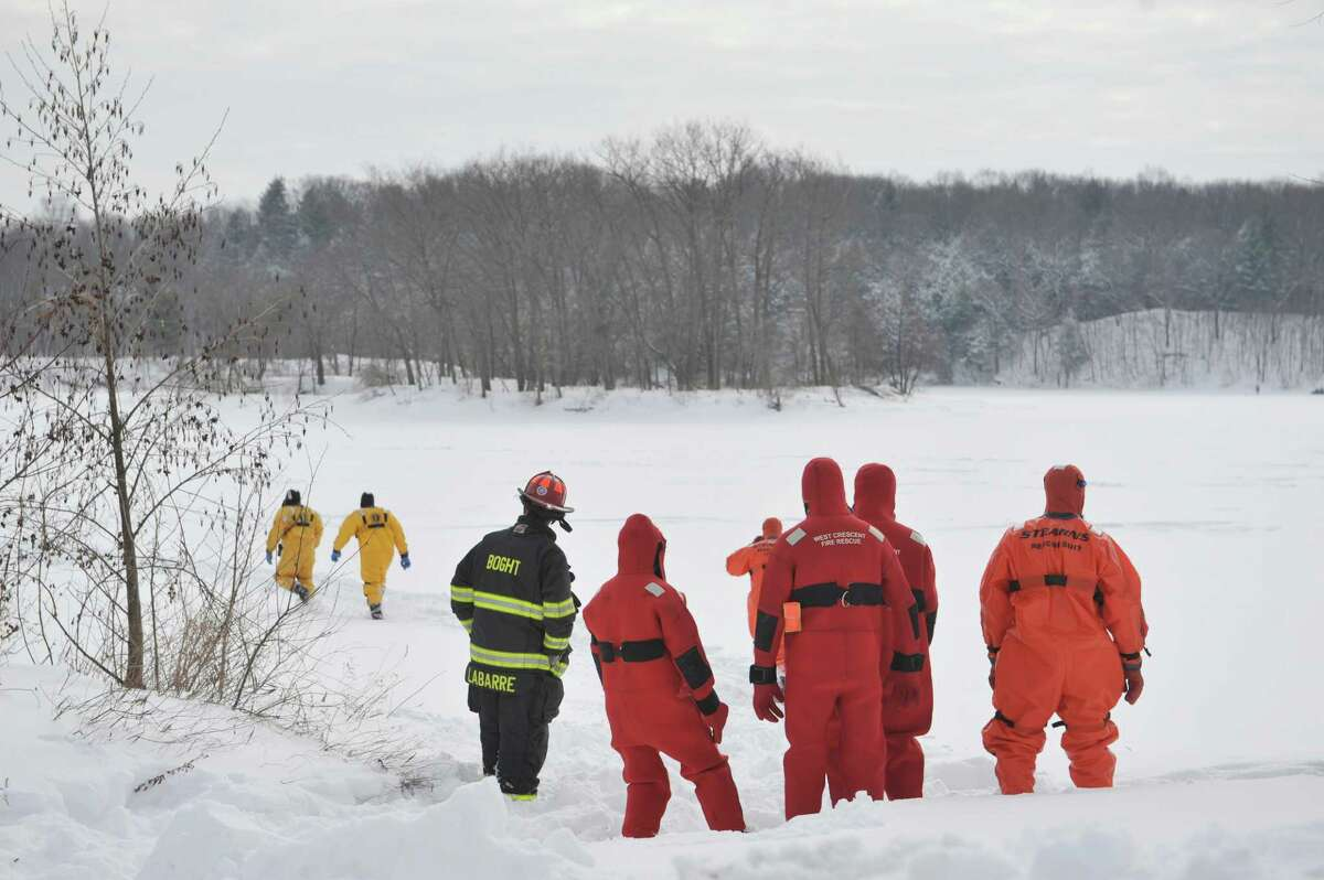 Firefighters dressed in water rescue suits head out onto the ice as members of the Boght Community Fire Department, Halfmoon-Waterford Fire Department and the West Crescent Fire Department take part in a cold weather water rescue drill on the Mohawk River on Sunday, Feb. 22, 2015, in Clifton Park, N.Y. (Paul Buckowski / Times Union)