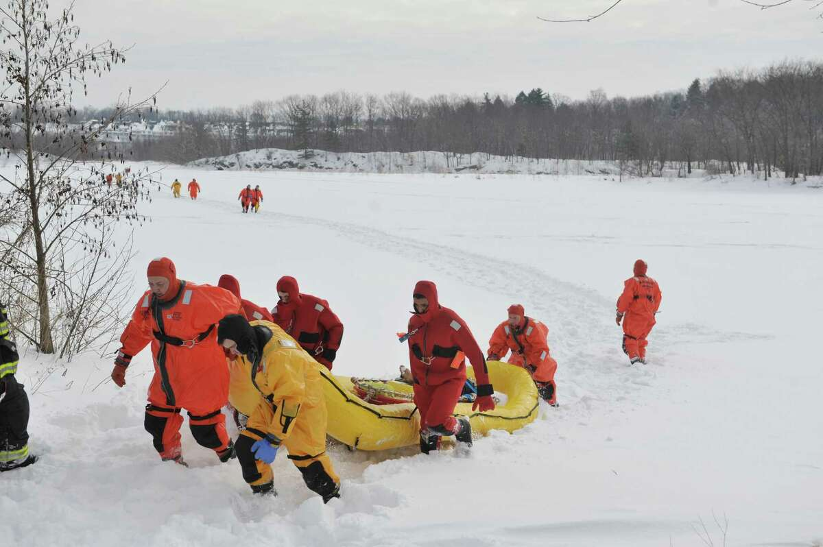 Firefighters dressed in water rescue suits drag a rescue sled back to shore as members of the Boght Community Fire Department, Halfmoon-Waterford Fire Department and the West Crescent Fire Department take part in a cold weather water rescue drill on the Mohawk River on Sunday, Feb. 22, 2015, in Clifton Park, N.Y. (Paul Buckowski / Times Union)