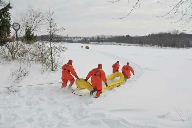 Firefighters dressed in water rescue suits drag a rescue sled out onto the ice as members of the Boght Community Fire Department, Halfmoon-Waterford Fire Department and the West Crescent Fire Department take part in a cold weather water rescue drill on the Mohawk River on Sunday, Feb. 22, 2015, in Clifton Park, N.Y.    (Paul Buckowski / Times Union) Photo: PAUL BUCKOWSKI / 00030717A