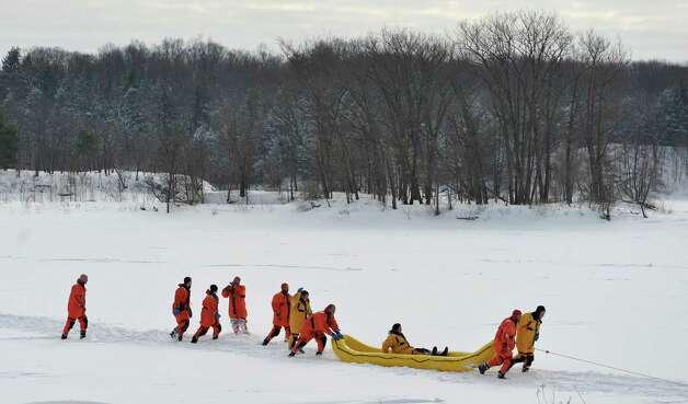 Firefighters dressed in water rescue suits use a rescue sled to transport a person to shore as members of the Boght Community Fire Department, Halfmoon-Waterford Fire Department and the West Crescent Fire Department take part in a cold weather water rescue drill on the Mohawk River on Sunday, Feb. 22, 2015, in Clifton Park, N.Y.    (Paul Buckowski / Times Union) Photo: PAUL BUCKOWSKI / 00030717A