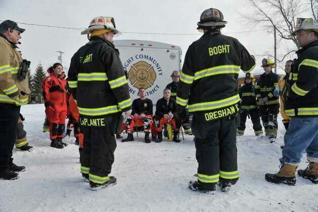 Firefighters discuss a rescue scenario they just took part in a members of the Boght Community Fire Department, Halfmoon-Waterford Fire Department and the West Crescent Fire Department take part in a cold weather water rescue drill on the Mohawk River on Sunday, Feb. 22, 2015, in Clifton Park, N.Y.    (Paul Buckowski / Times Union) Photo: PAUL BUCKOWSKI / 00030717A