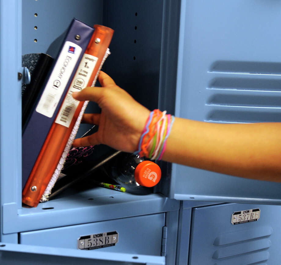 Eighth grader Ashadeya Davis removes items from her locker at the Myers Middle School in Albany, New York as students clean out their lockers June 16, 2010,  which is perceived as the annual rite of passage for the students who will begin as freshman in high school next year.   (Skip Dickstein/Times Union) Photo: Skip Dickstein / 2008