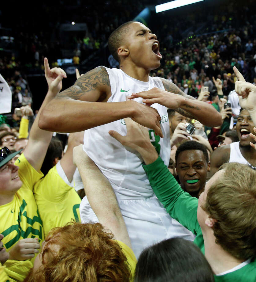 Oregon's Joseph Young is hoisted by fans in Eugene after the Ducks defeated No. 9 Utah 69-58. Photo: Andy Nelson / Associated Press / The Register-Guard