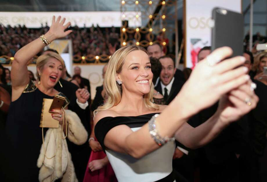 Reese Witherspoon takes a selfie at the 87th Annual Academy Awards at Hollywood & Highland Center in Hollywood. She wears an off the shoulder white dress with two black straps, one along the top and the other at the waist. Photo: Christopher Polk /Getty Images / 2015 Getty Images