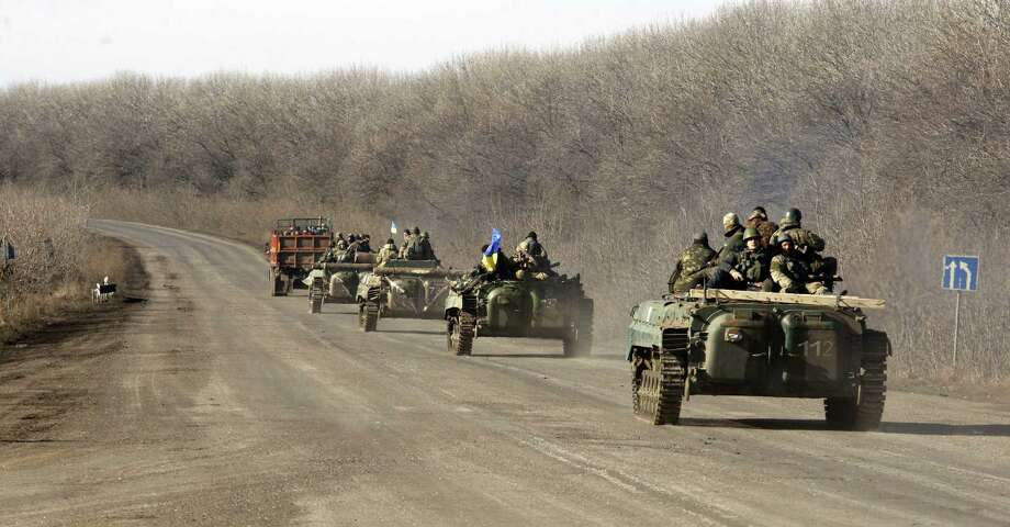 A column of Ukrainian forces rides on February 22, 2015 near Artemivsk, in the Donetsk region, eastern Ukraine.  The Ukrainian army and the rebels announced on Sunday, they had agreed to pull back heavy weapons from the frontline, an important and overdue part of the truce. But the only visible sign of compliance with the ceasefire agreement was a late-Saturday prisoner swap of nearly 200 fighters detained by both sides. AFP PHOTO/ANATOLII STEPANOVANATOLII STEPANOV/AFP/Getty Images Photo: ANATOLII STEPANOV, Stringer / AFP / Getty Images / AFP