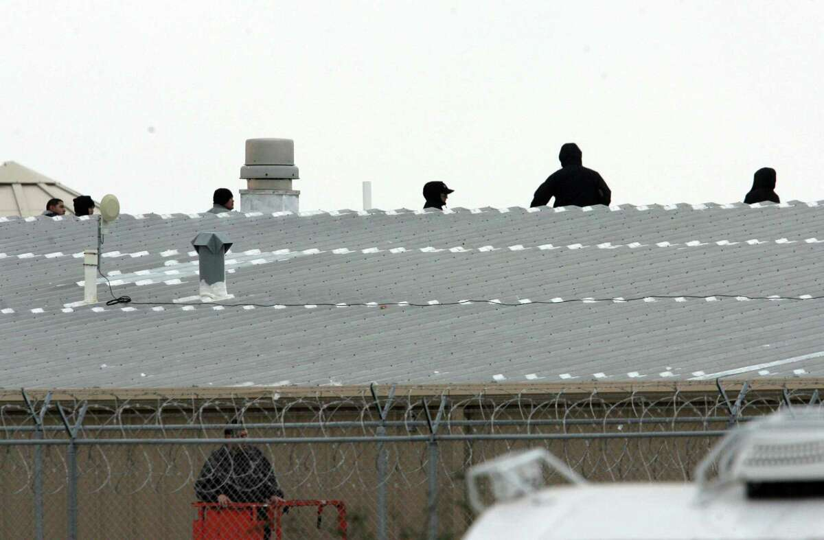 """Correctional guards at the Willacy County Correctional Center in Raymondville, Texas peer from the roof top Saturday Feb.21, 2015. Ed Ross, a spokesman for the U.S. Bureau of Prisons, said the inmates who had taken control are """"now compliant"""" but that negotiations were ongoing Saturday in an effort for staff to """"regain complete control"""" of Willacy County Correctional Center.Photo by Delcia Lopez"""