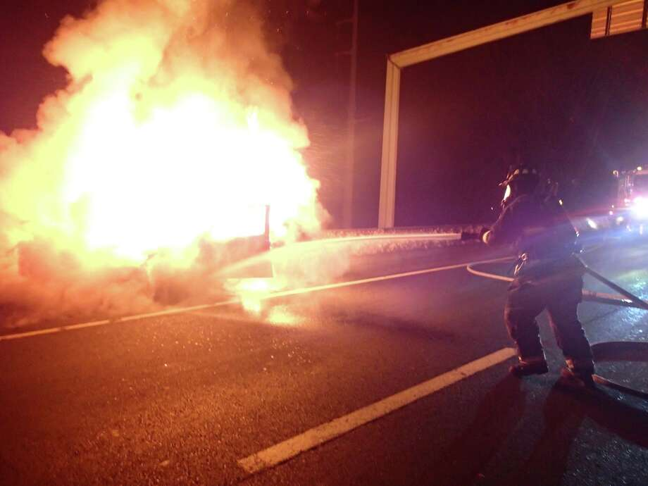 Firefighters on the scene of a car that was engulfed in flames on Interstate 95 Sunday night, between northbound Exits 18 and 19. The driver escaped without injuries. Photo: Westport Fire Department / Westport News