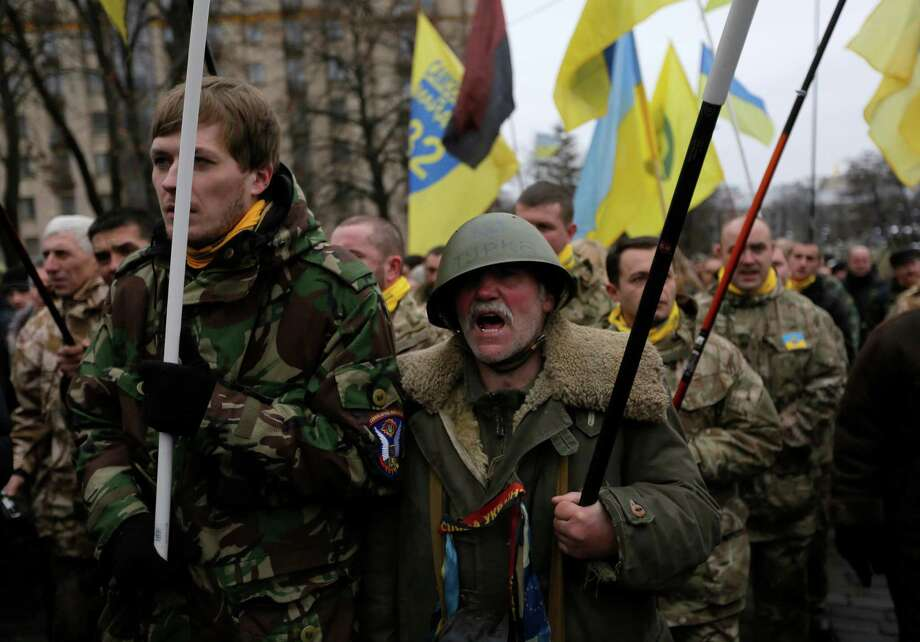 People shout slogans as they march in Kiev on Sunday. Thousands participated in the march to commemorate the events of a year ago and honoring the more than 100 protesters who died in the violence. Photo: Sergei Chuzavkov, STF / AP